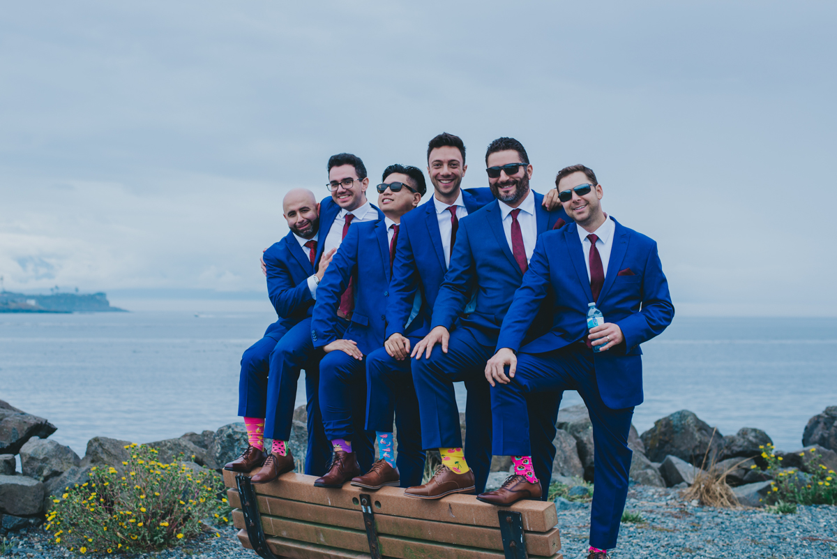 Persian-Canadian Wedding Innocent Thunder Photography Sooke Victoria Canada amin and groomsmen standing on bench showing off colorful socks