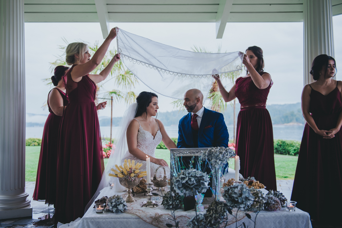 Persian-Canadian Wedding Innocent Thunder Photography Sooke Victoria Canada bridesmaids holding lace above couple
