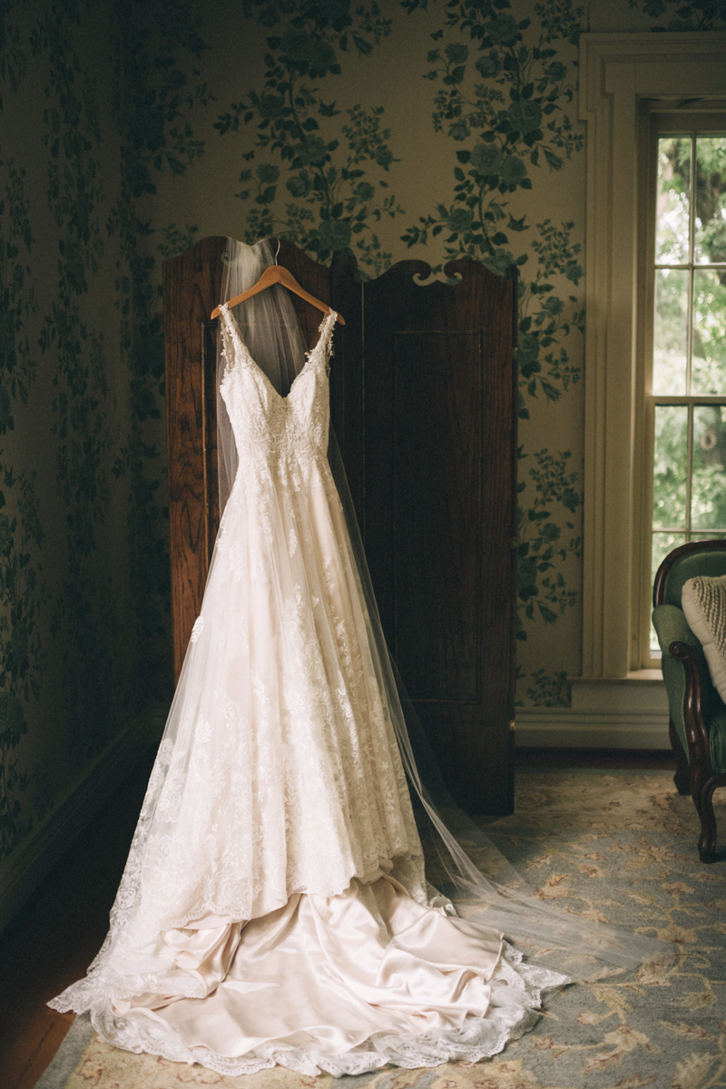 Warrenwood manor danville kentucky wedding sarah katherine davis dress hanging from wooden screen