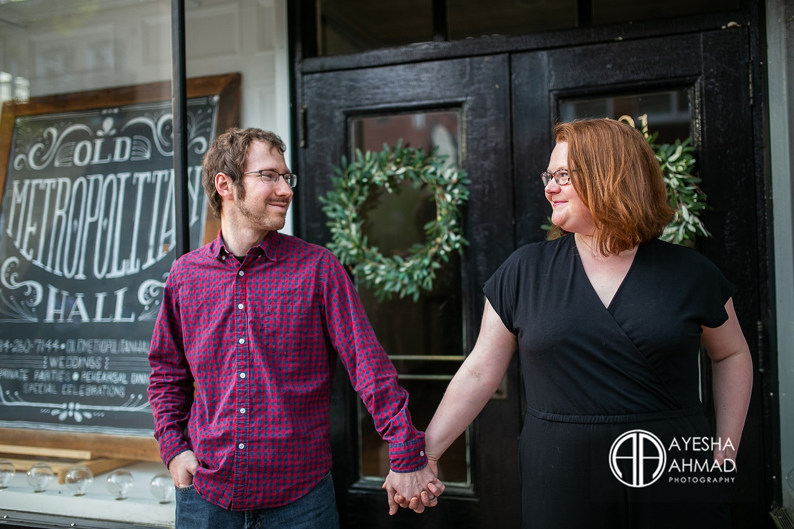 Jen and cameron hold hands in front of Old Metropolitan Hall during couples session in Downtown Charlottesville Ayesha Ahmad Photography