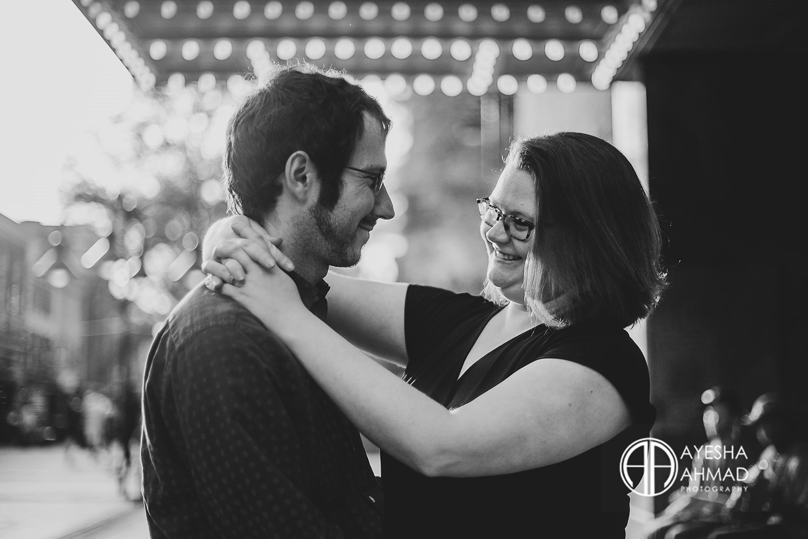Jen and cameron embrace in front of The Paramount Theatre during couples session in Downtown Charlottesville Virginia Ayesha Ahmad Photography