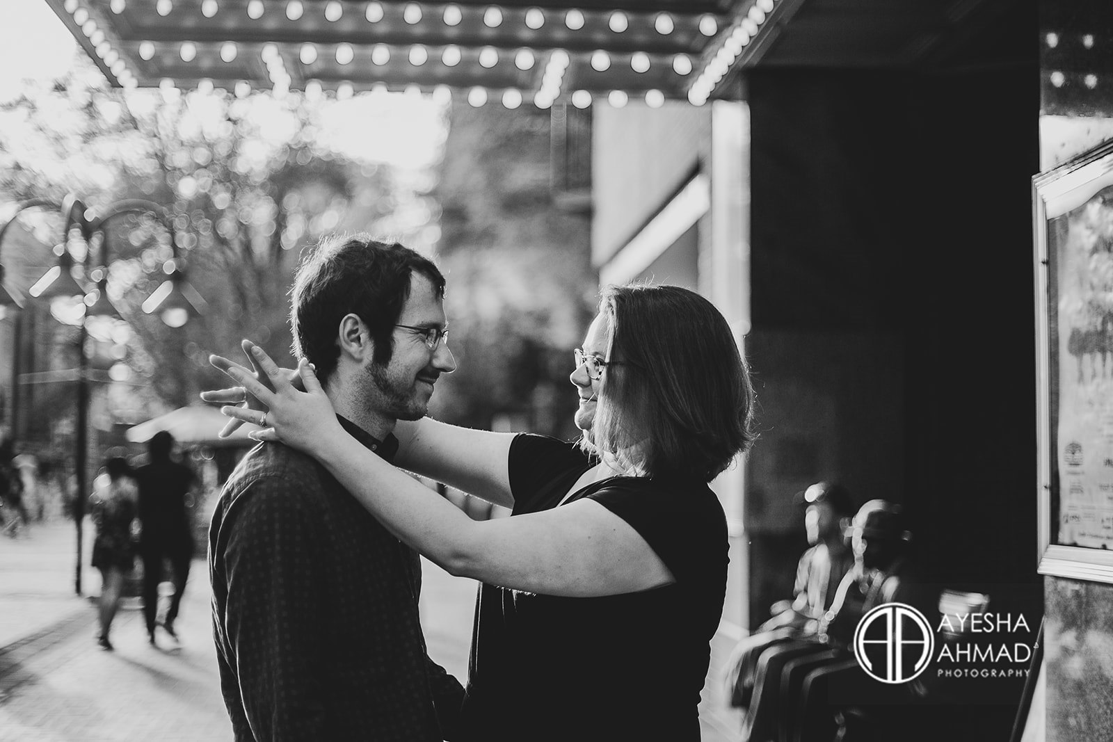 Jen and cameron hold embrace in front of The Paramount Theatre during couples session in Downtown Charlottesville Virginia Ayesha Ahmad Photography