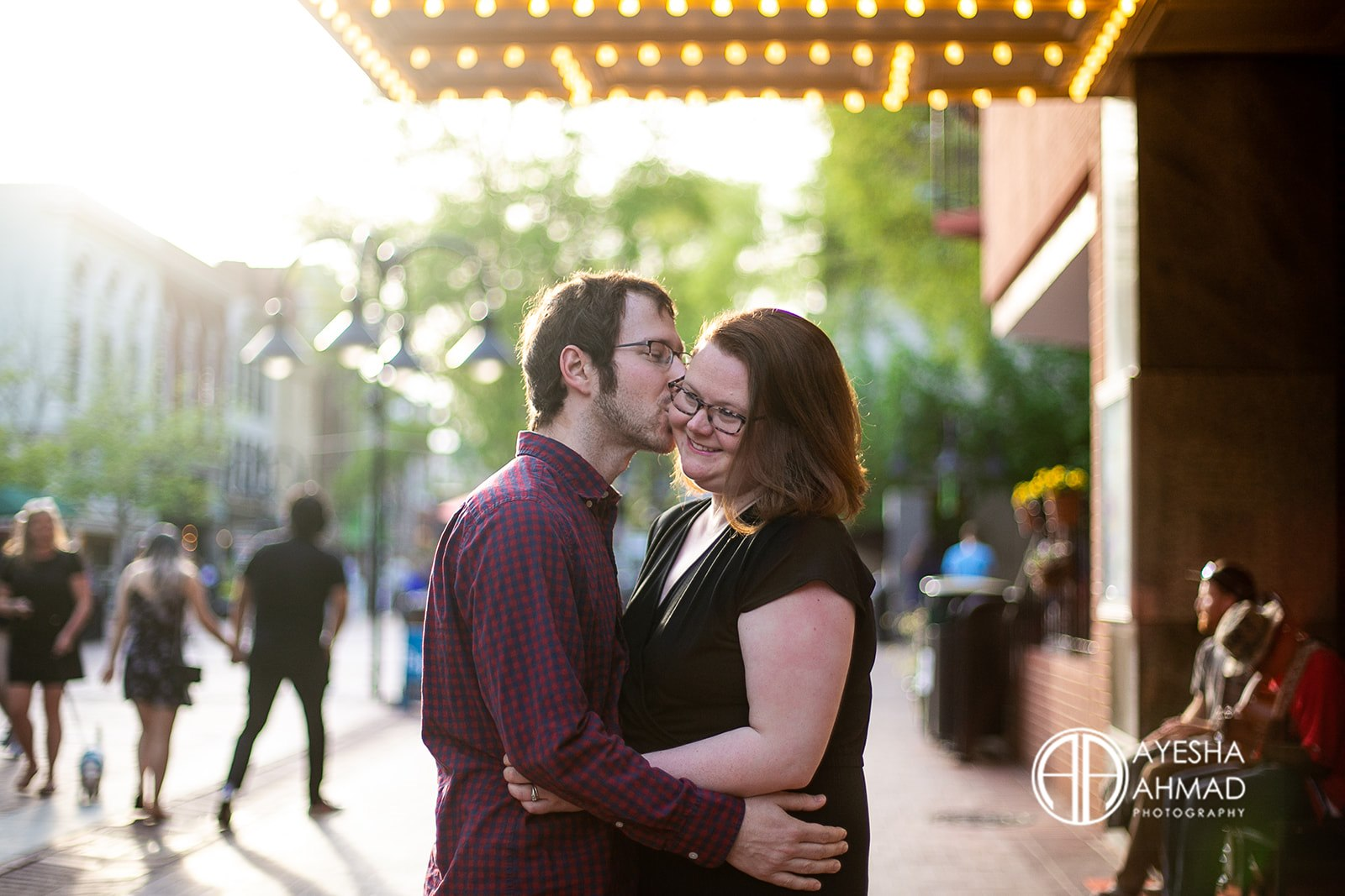 Jen and cameron kiss in front of The Paramount Theatre during couples session in Downtown Charlottesville Virginia Ayesha Ahmad Photography