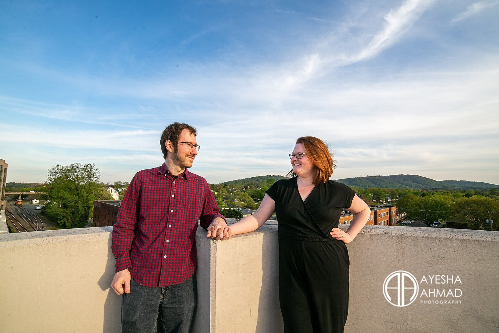 Jen and cameron hold hands with Carter Mountain and Monticello in background during couples session in Downtown Charlottesville Virginia Ayesha Ahmad Photography