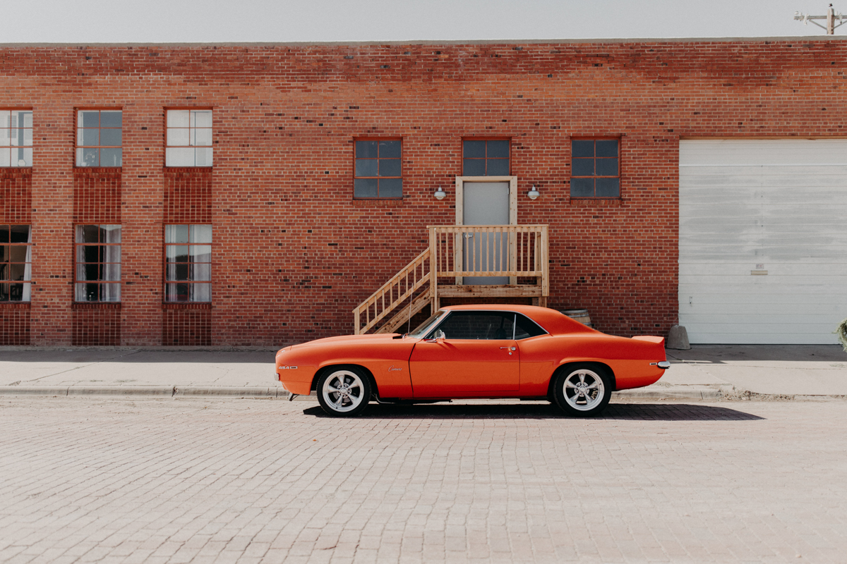 ABBY AND NICK WEDDING AMARILLO TX RITTER COLLECTIVE PHOTOGRAPHY ORANGE 1969 CAMARO PARKED ON STREET