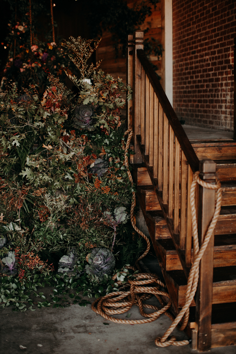 ABBY AND NICK WEDDING AMARILLO TX RITTER COLLECTIVE PHOTOGRAPHY WOODEN STAIRCASE NEXT TO FLOWER WALL