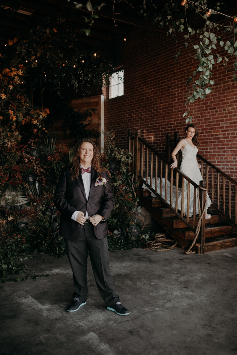 ABBY AND NICK WEDDING AMARILLO TX RITTER COLLECTIVE PHOTOGRAPHY ABBY IN FRONT OF FLOWERS AND NICK DESCENDING STAIRS
