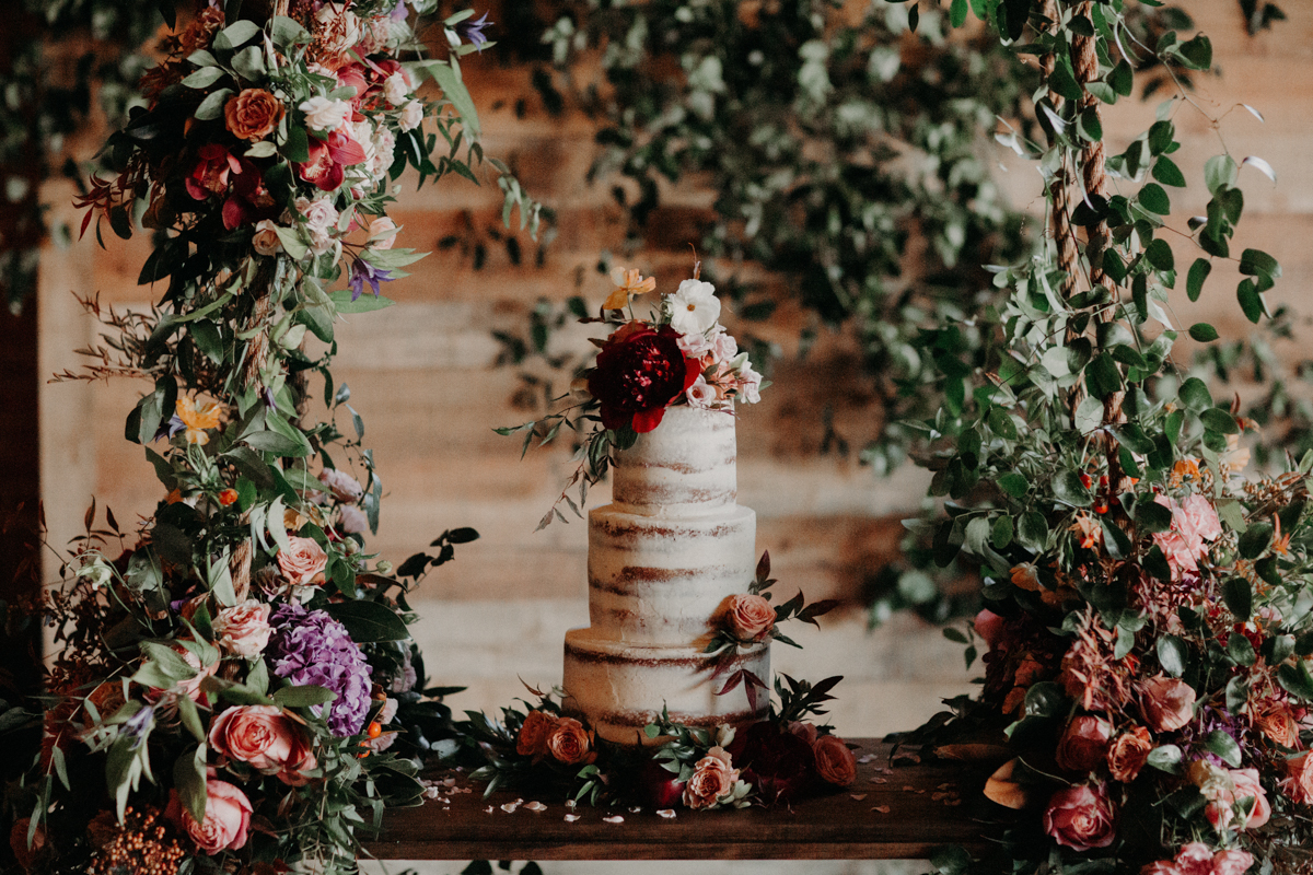 ABBY AND NICK WEDDING AMARILLO TX RITTER COLLECTIVE PHOTOGRAPHY WEDDING CAKE WITH FLOWERS ON SWING