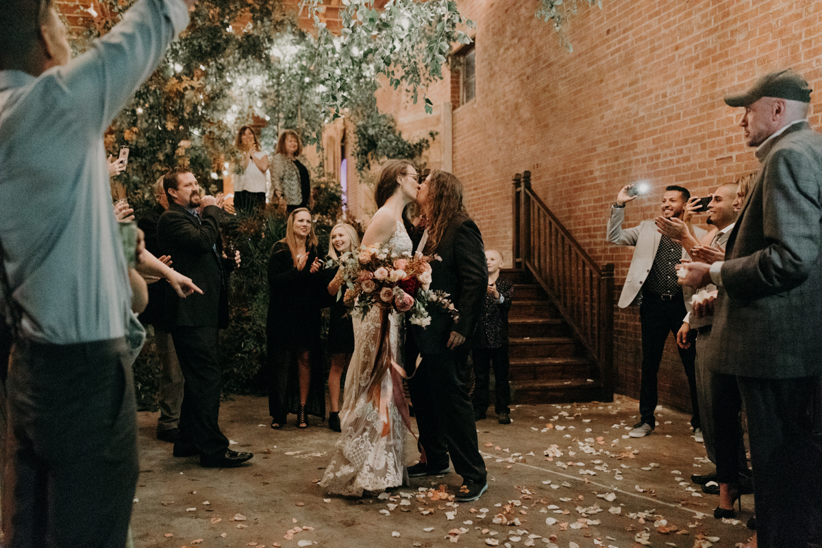 ABBY AND NICK WEDDING AMARILLO TX RITTER COLLECTIVE PHOTOGRAPHY COUPLE KISSES AS GUESTS CHEER
