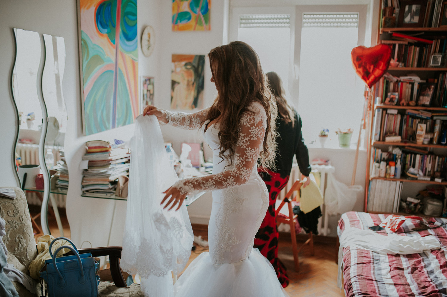 Sofia getting ready in DIY wedding dress surrounded by parents' paintings serbia Aleska and Mina Photography