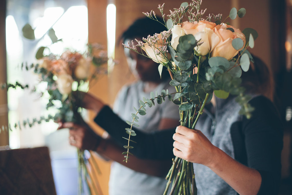 Brides and guests help assemble bouquets before DIY wedding in Colorado Cassandra Zetta Photography
