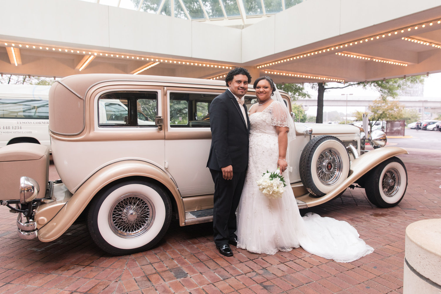 bride and groom stand in front of vintage car at their DIY wedding Photography by Marirosa