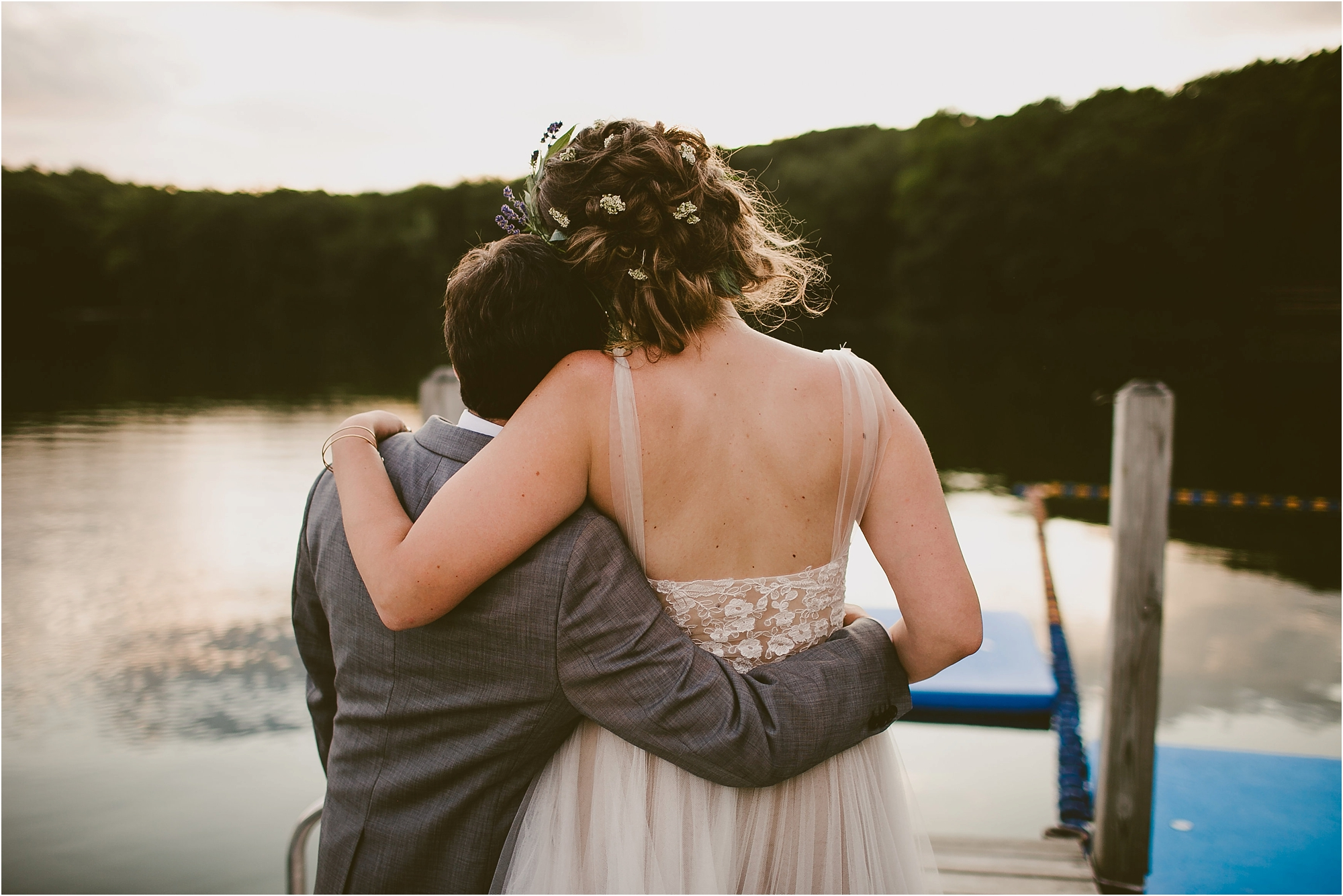 bride and groom hug by lake at diy wedding in the woods Emily Dykema