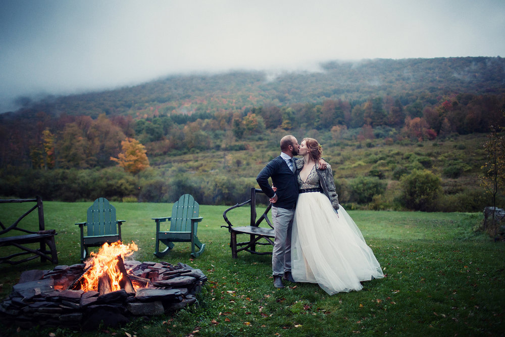 bride and groom kiss by firepit during their DIY catskills wedding Ella Sophia Photo