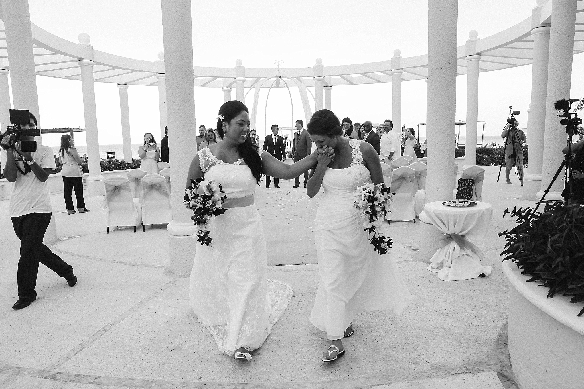 brides exit ceremony holding DIY bouquets Mexico LGBTQ wedding Leah Moyers Photography