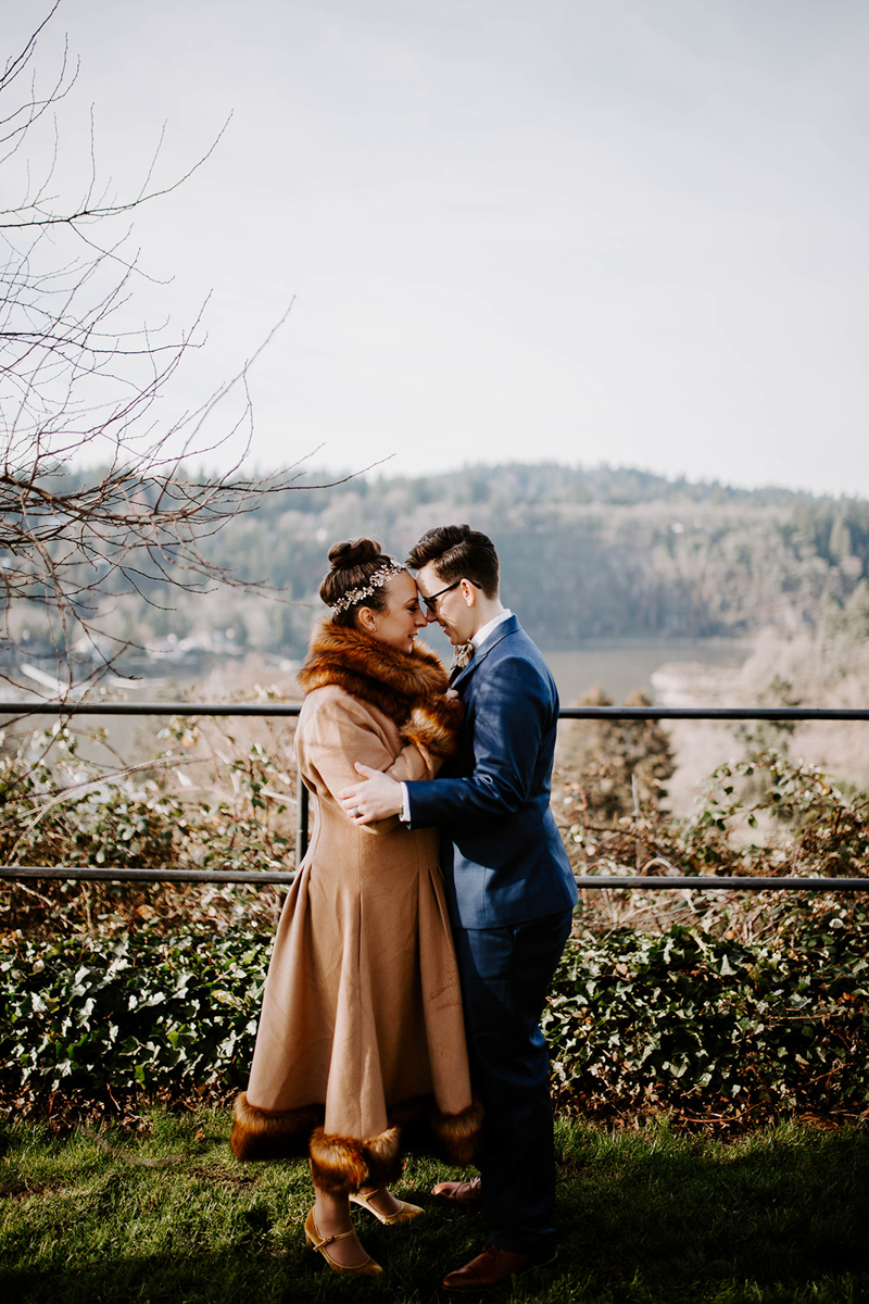 Couple embrace outside home overlooking river before their DIY surprise wedding Jamie Carle