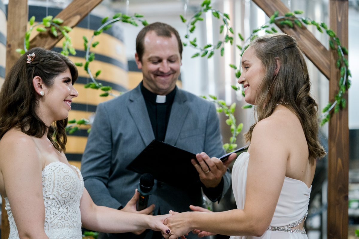 brides exchange rings in front of altar with DIY hops wreaths Love Life Images