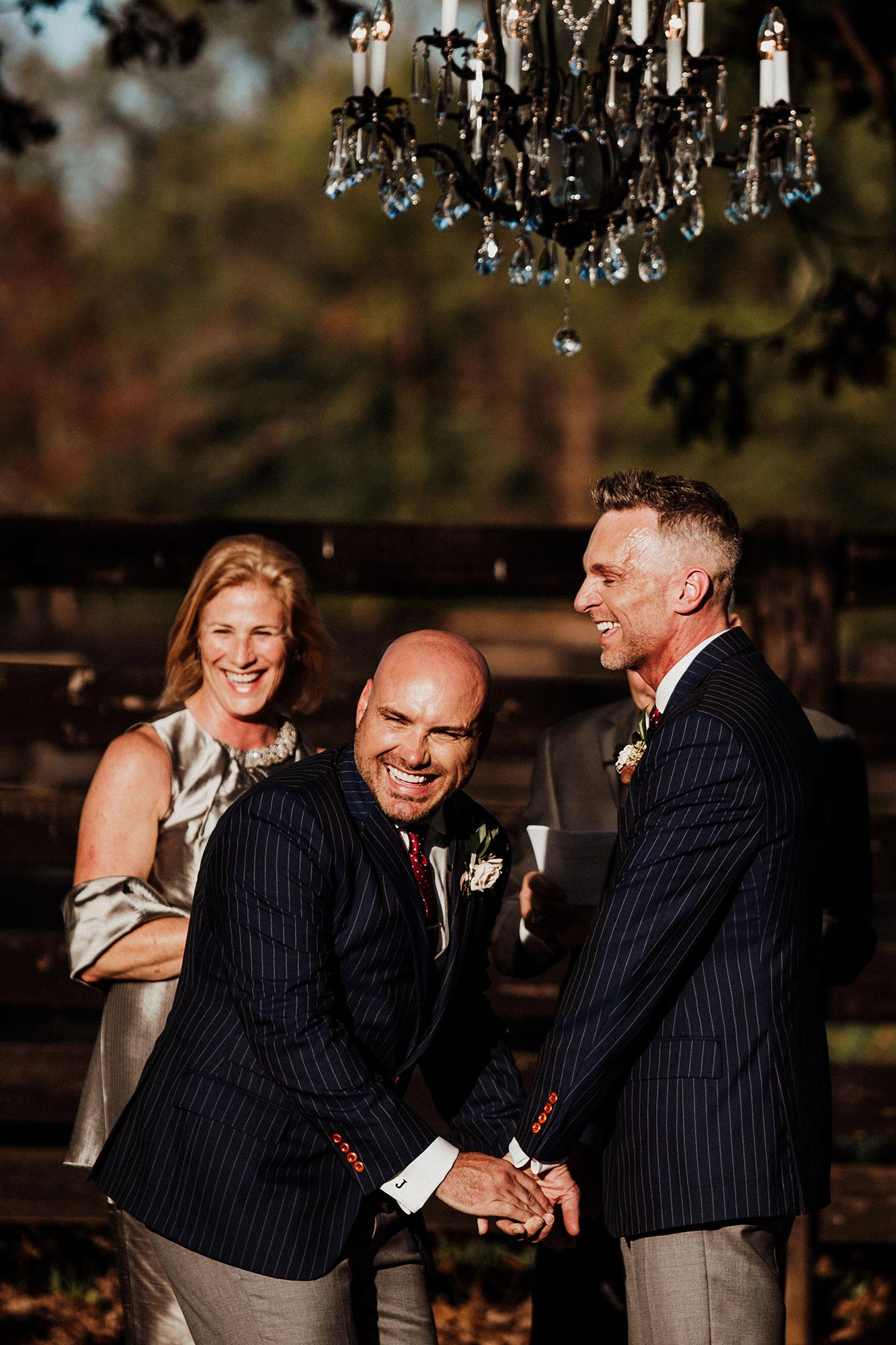 LGBTQ Louisville Kentucky Wedding at Hermitage Farm Crystal Ludwick Photo grooms laughing and holding hands during ceremony