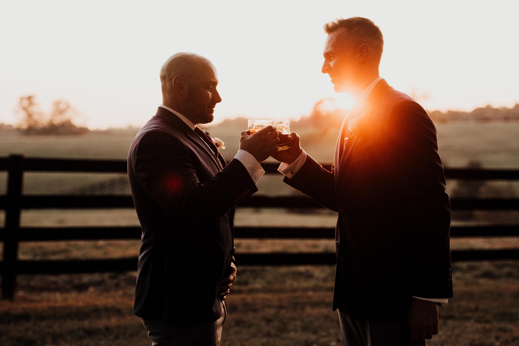 LGBTQ Louisville Kentucky Wedding at Hermitage Farm Crystal Ludwick Photo couple sharing bourbon by fence