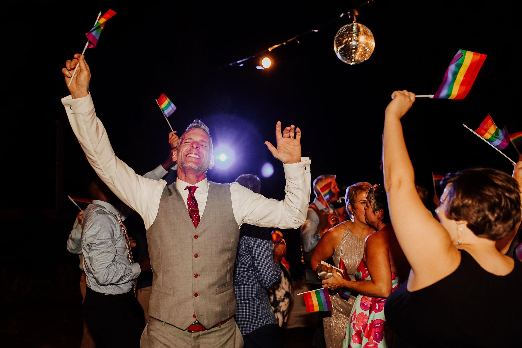 LGBTQ Louisville Kentucky Wedding at Hermitage Farm Crystal Ludwick Photo groom and guests waving rainbow flags on dance floor
