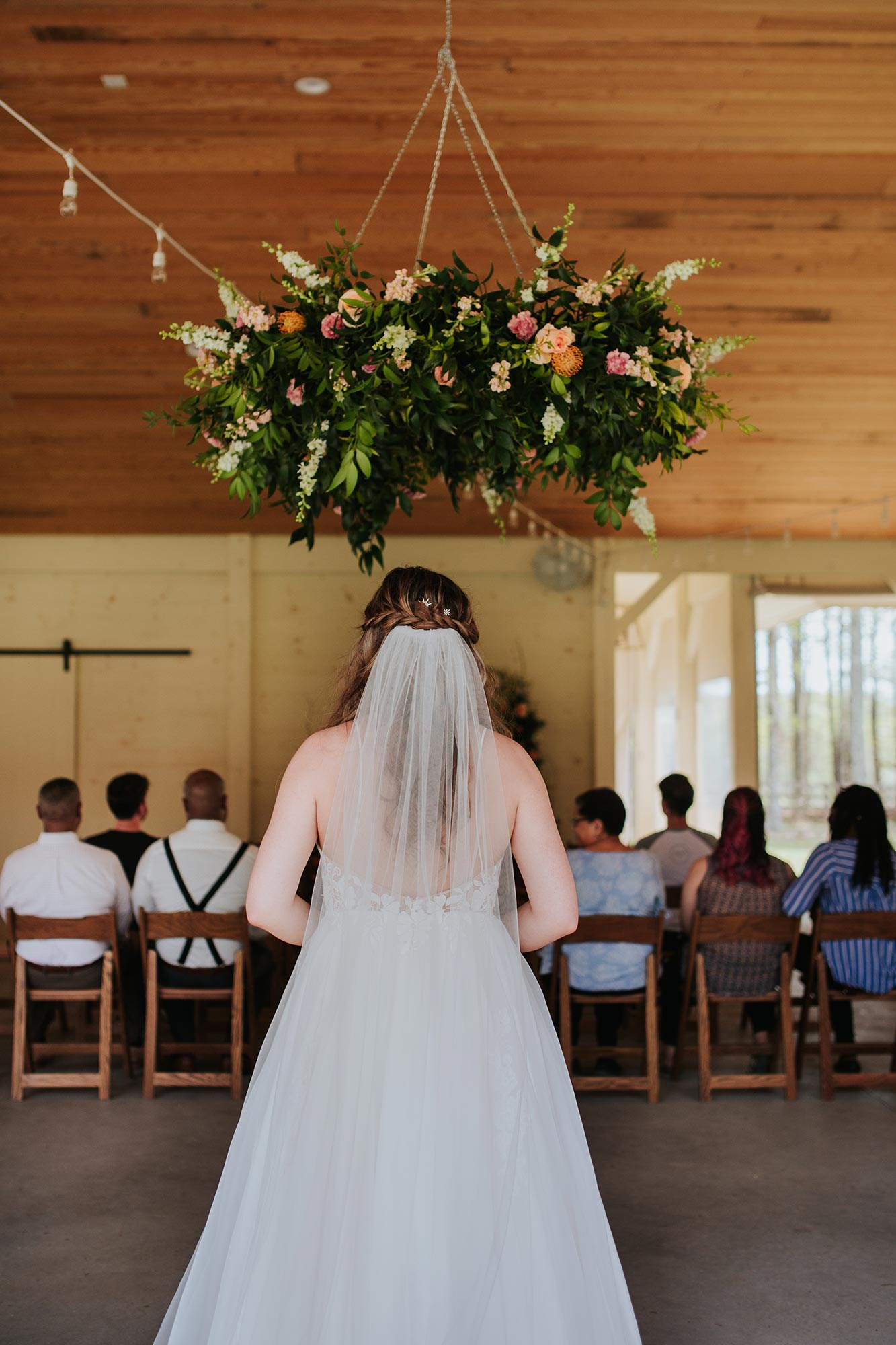 Lush wedding inspiration at Seven Springs VA with bride walking into ceremony under floral chandelier Carly Romeo & Co.
