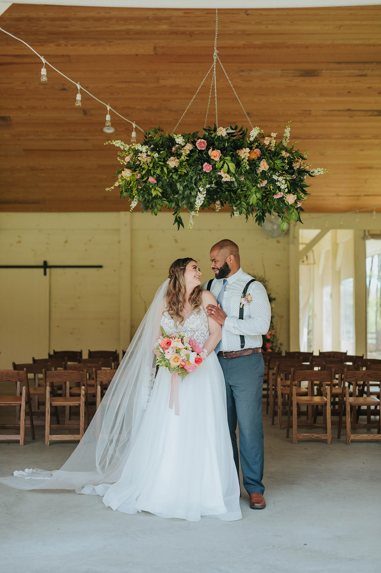 Lush wedding inspiration at Seven Springs VA with bride and groom under floral chandelier Carly Romeo & Co.