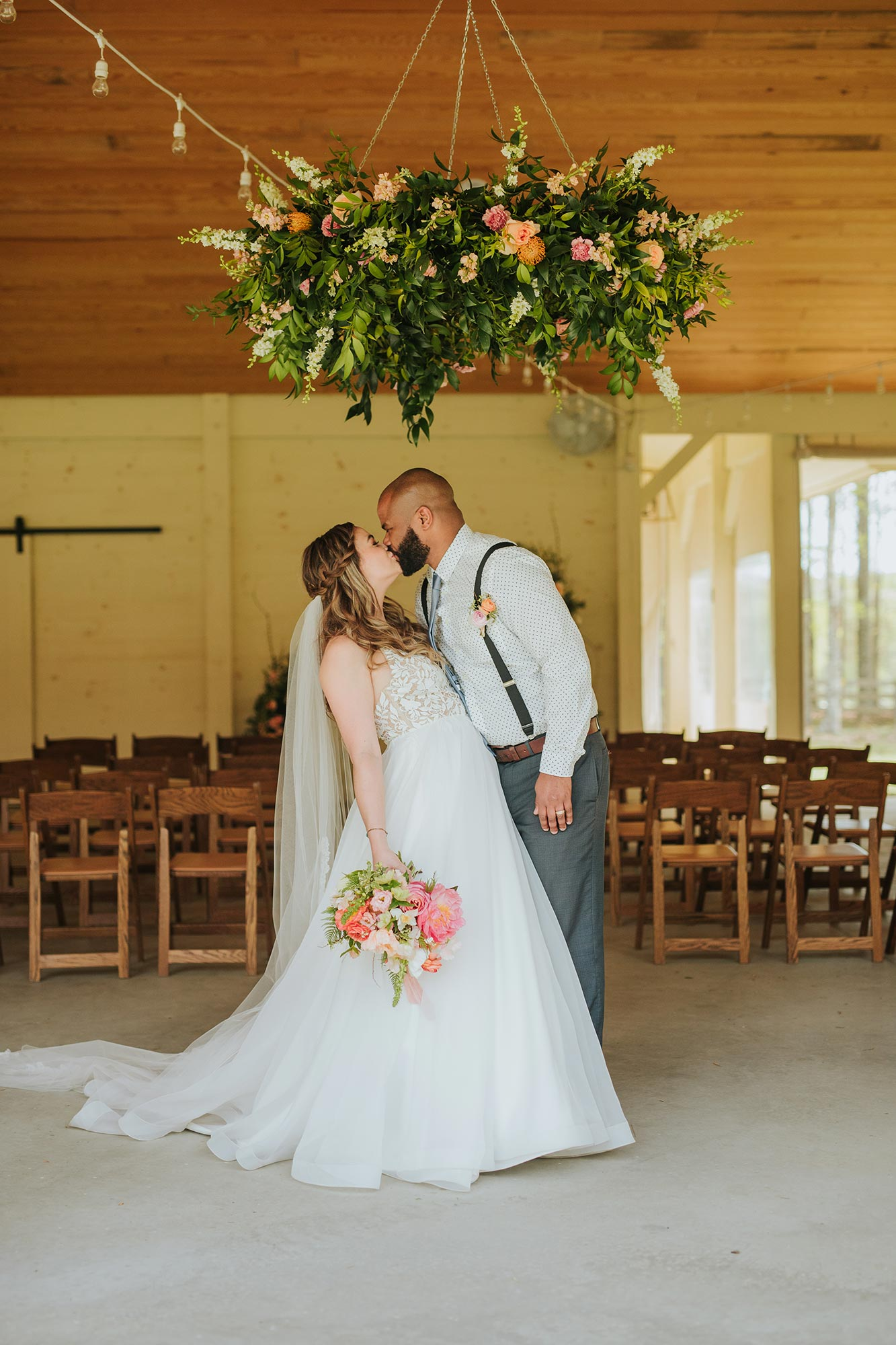Lush wedding inspiration at Seven Springs VA with bride and groom kissing under floral chandelier Carly Romeo & Co.