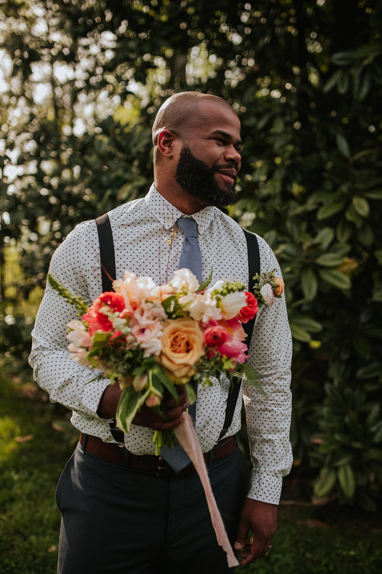 Lush wedding inspiration at Seven Springs VA with groom smiling and holding bouquet Carly Romeo & Co.