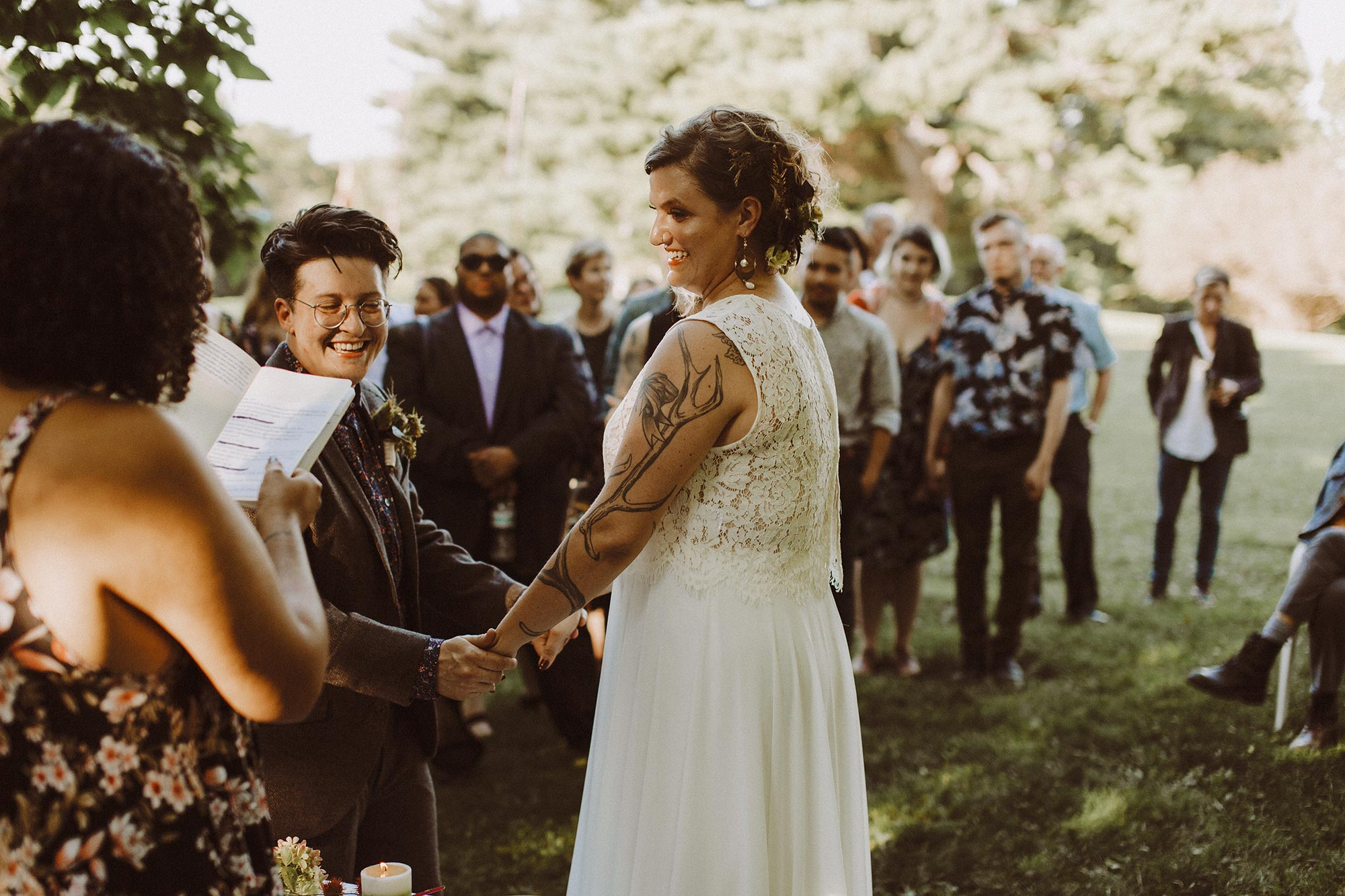 DIY summer camp wedding spring green wisconsin heidi uhlman photography couple smiling and holding hands during ceremony
