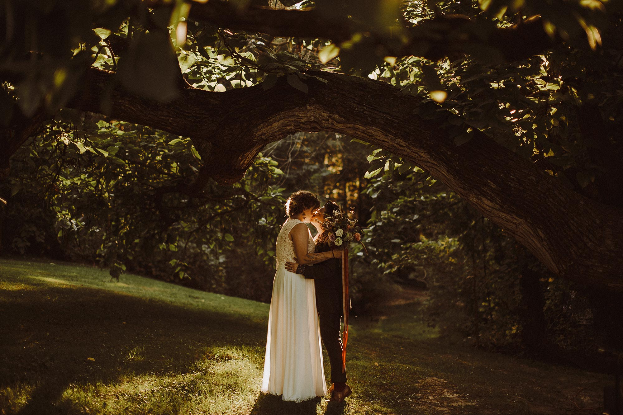 DIY summer camp wedding spring green wisconsin heidi uhlman photography alex and frances kiss under tree