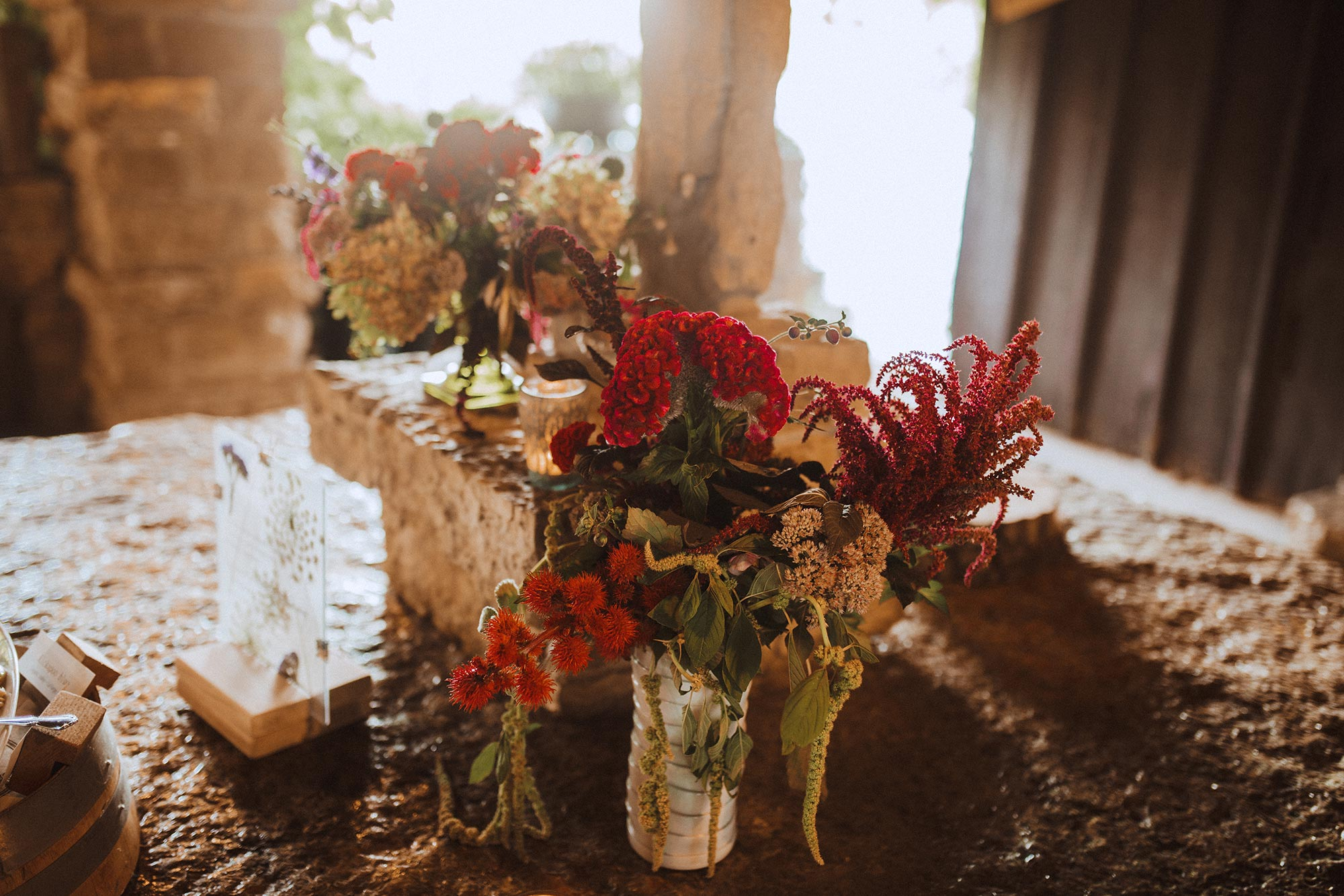 DIY summer camp wedding spring green wisconsin heidi uhlman photography flowers in vases on slab of rock