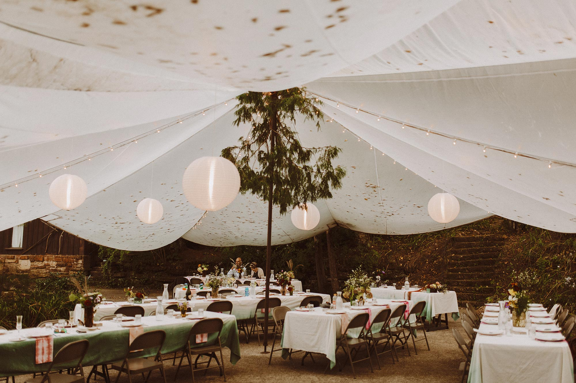DIY summer camp wedding spring green wisconsin heidi uhlman photography guest tables with gauzy white tent ceiling