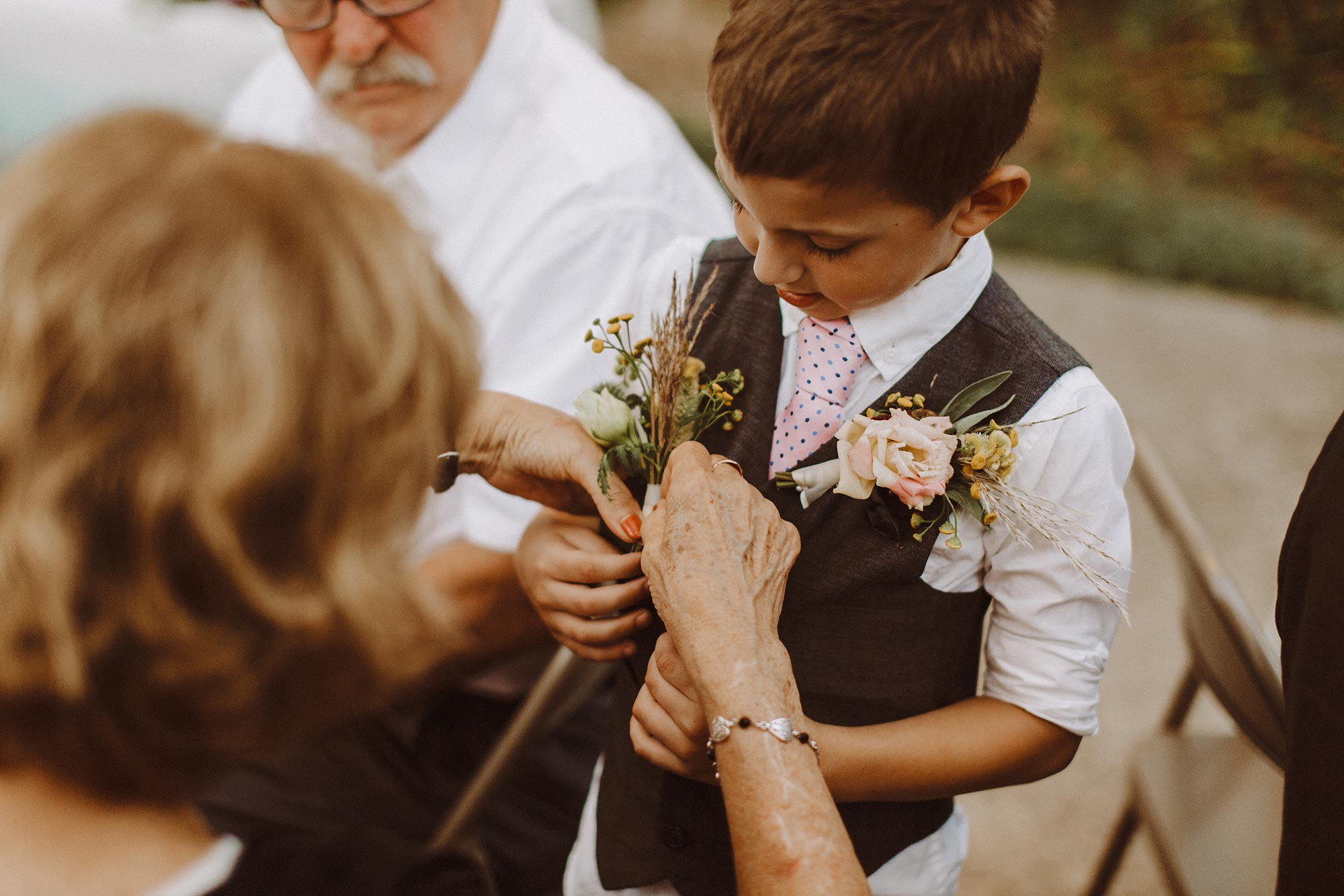 DIY summer camp wedding spring green wisconsin heidi uhlman photography young guest getting help with boutonniere