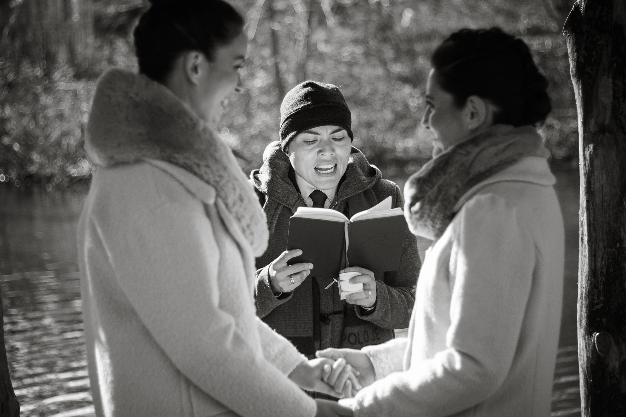 queer irish central park winter elopement kate alison photography officiant karla and brides holding hands by lake