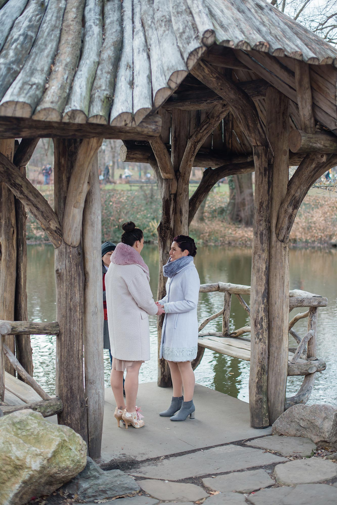 queer irish central park winter elopement kate alison photography couple and officiant under log shelter by river for ceremony