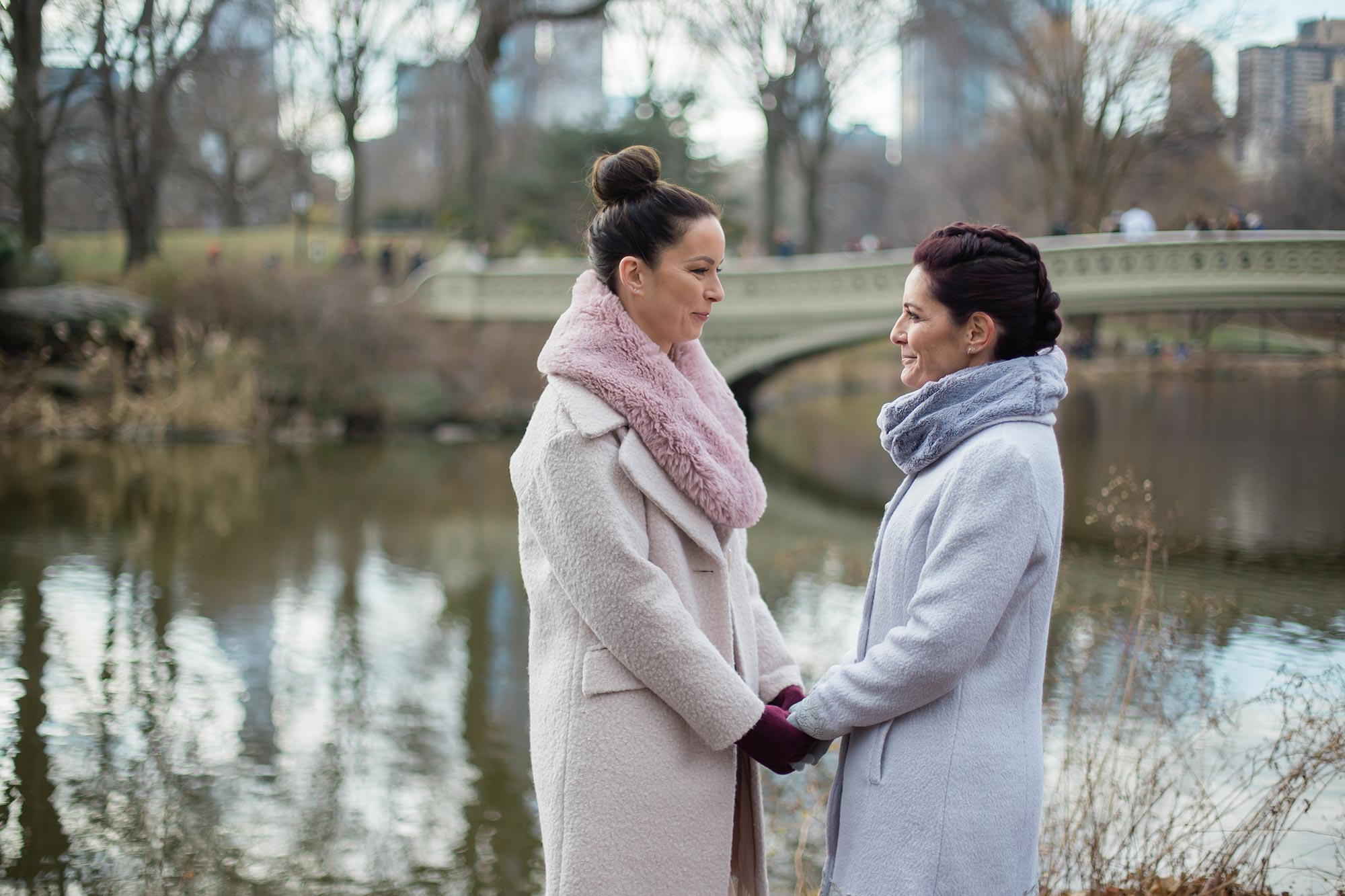 queer irish central park winter elopement kate alison photography brides holding hands by lake, bridge in background