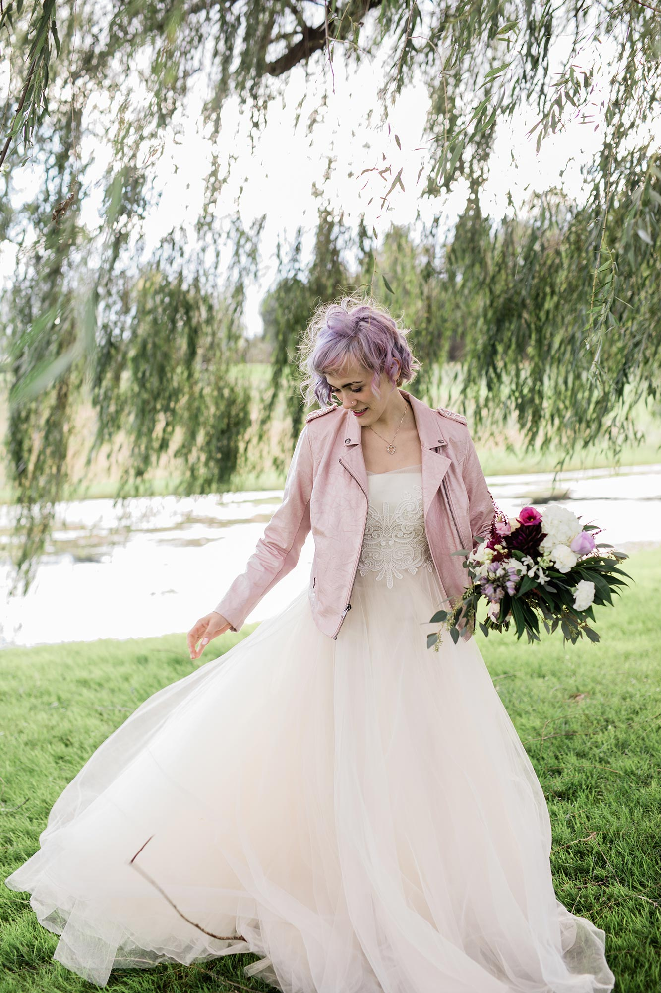 Chic Queer Wedding in West Chester Pennsylvania showing Sara in wedding dress and pink leather jacket with bouquet Judson Rappaport Photography
