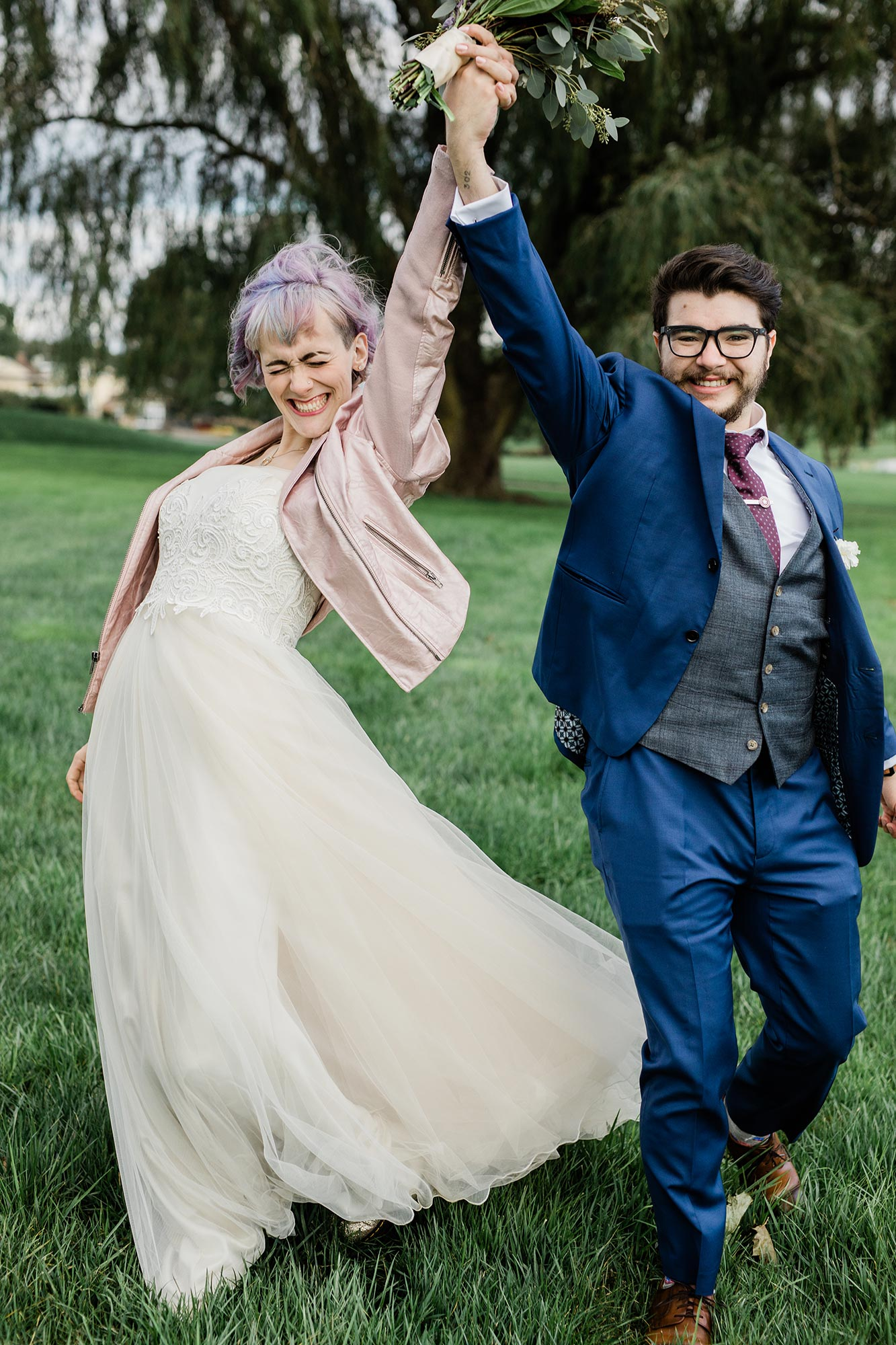 Chic Queer Wedding in West Chester Pennsylvania showing couple holding hands in air Judson Rappaport Photography