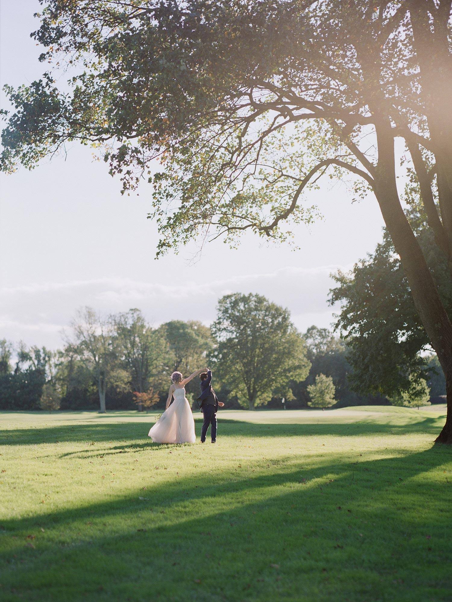 Chic Queer Wedding in West Chester Pennsylvania showing couple dancing in a field Judson Rappaport Photography