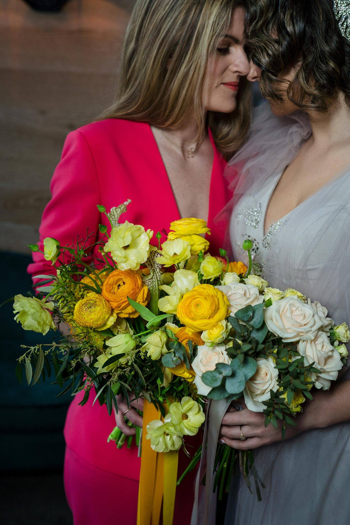 Bright Neon Wedding Inspiration at The Bowery Hotel NYC showing coupld in gray dress and neon pink suit holding yellow bouquets JC Lemon Photography