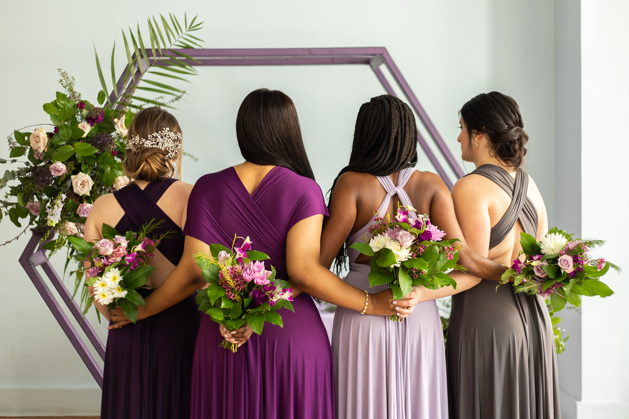 Henkaa fall wedding party dresses in purple and gray tones with bridesmaids holding bouquets