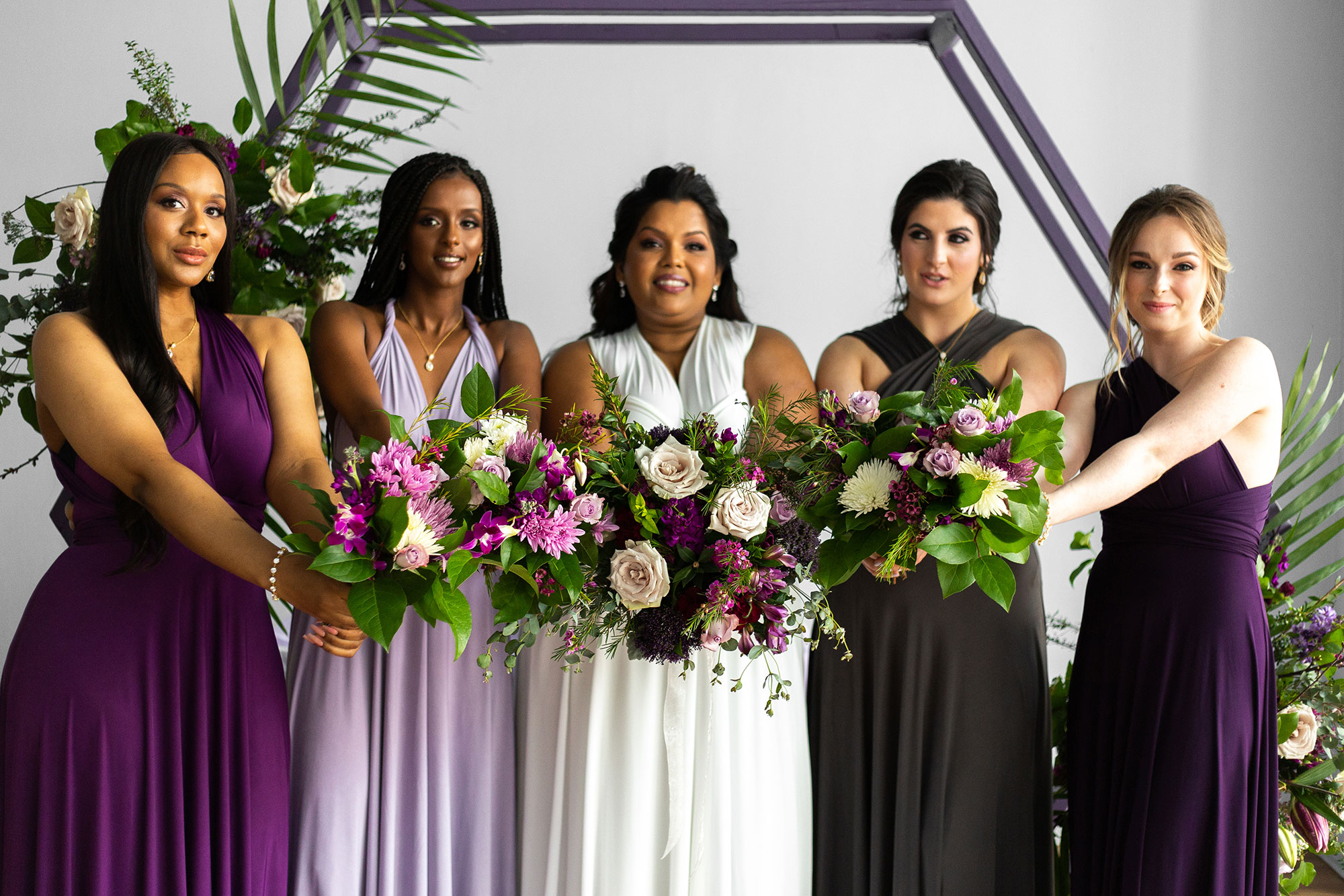 Henkaa fall wedding party dresses in purple and gray tones with bride in white and bridesmaids holding bouquets