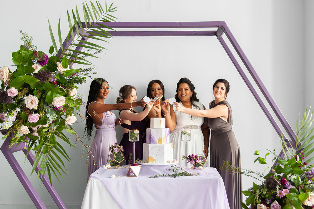 Henkaa fall wedding party dresses in purple and gray tones with bride in white all holding up cookies in front of cake