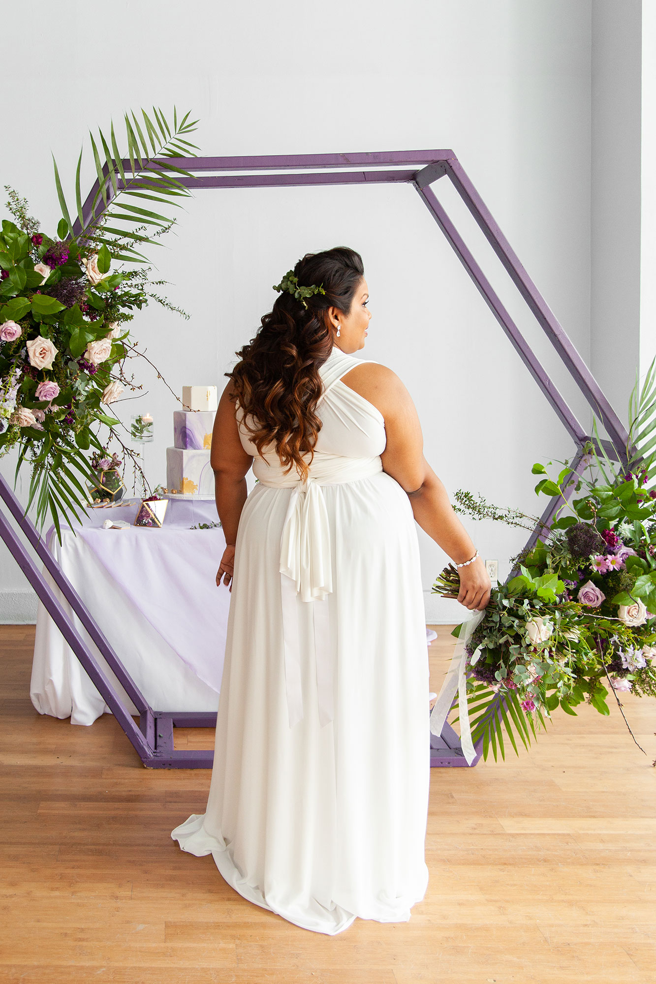 Henkaa fall wedding collection with bride in white showing back of dress while holding bouquet