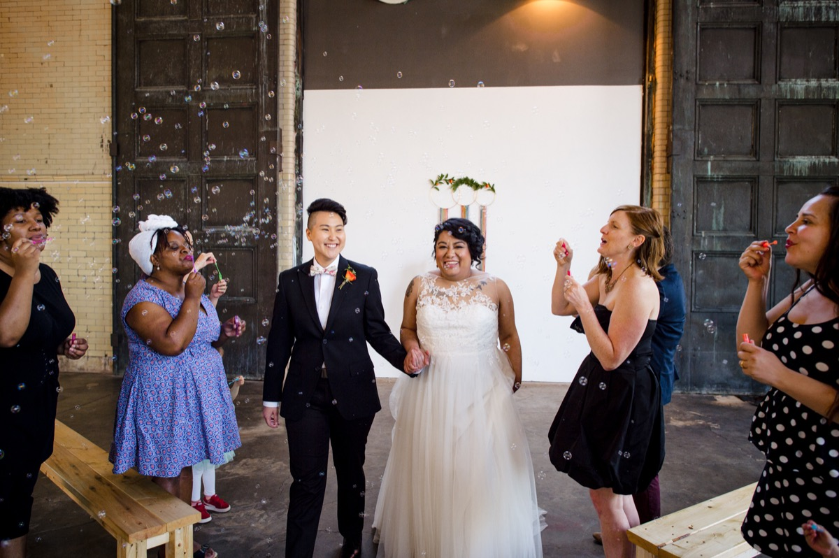 RAINBOW QUEER WEDDING INSPIRATION MICHELLE SCHAPIRO, DEANNA NAGLE, guests blowing bubbles as couple walks up aisle
