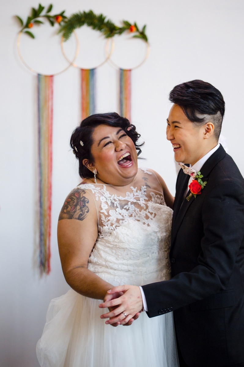 RAINBOW QUEER WEDDING INSPIRATION MICHELLE SCHAPIRO, DEANNA NAGLE, laughing candid by rainbow hoops