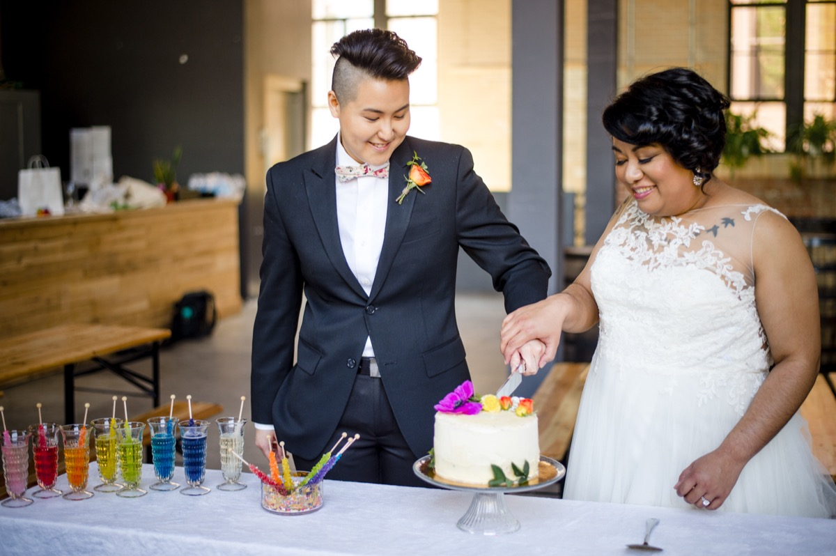 RAINBOW QUEER WEDDING INSPIRATION MICHELLE SCHAPIRO, DEANNA NAGLE, couple cutting cake