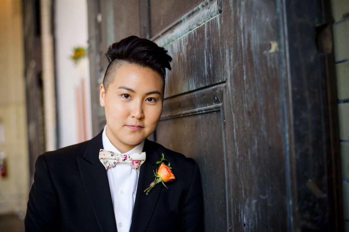 RAINBOW QUEER WEDDING INSPIRATION MICHELLE SCHAPIRO, DEANNA NAGLE, model wearing suit by weathered door