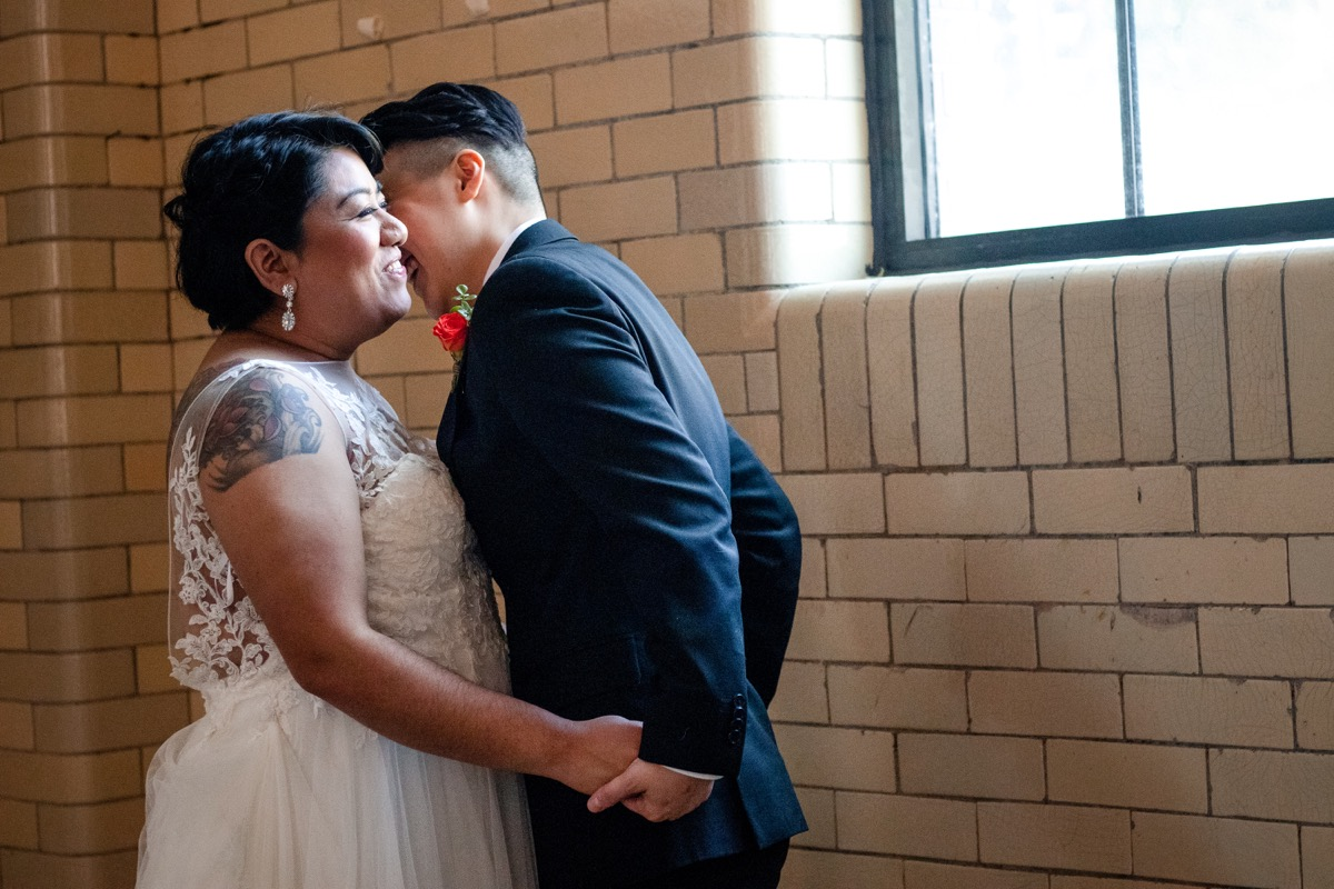 RAINBOW QUEER WEDDING INSPIRATION MICHELLE SCHAPIRO, DEANNA NAGLE, couple laughing by window