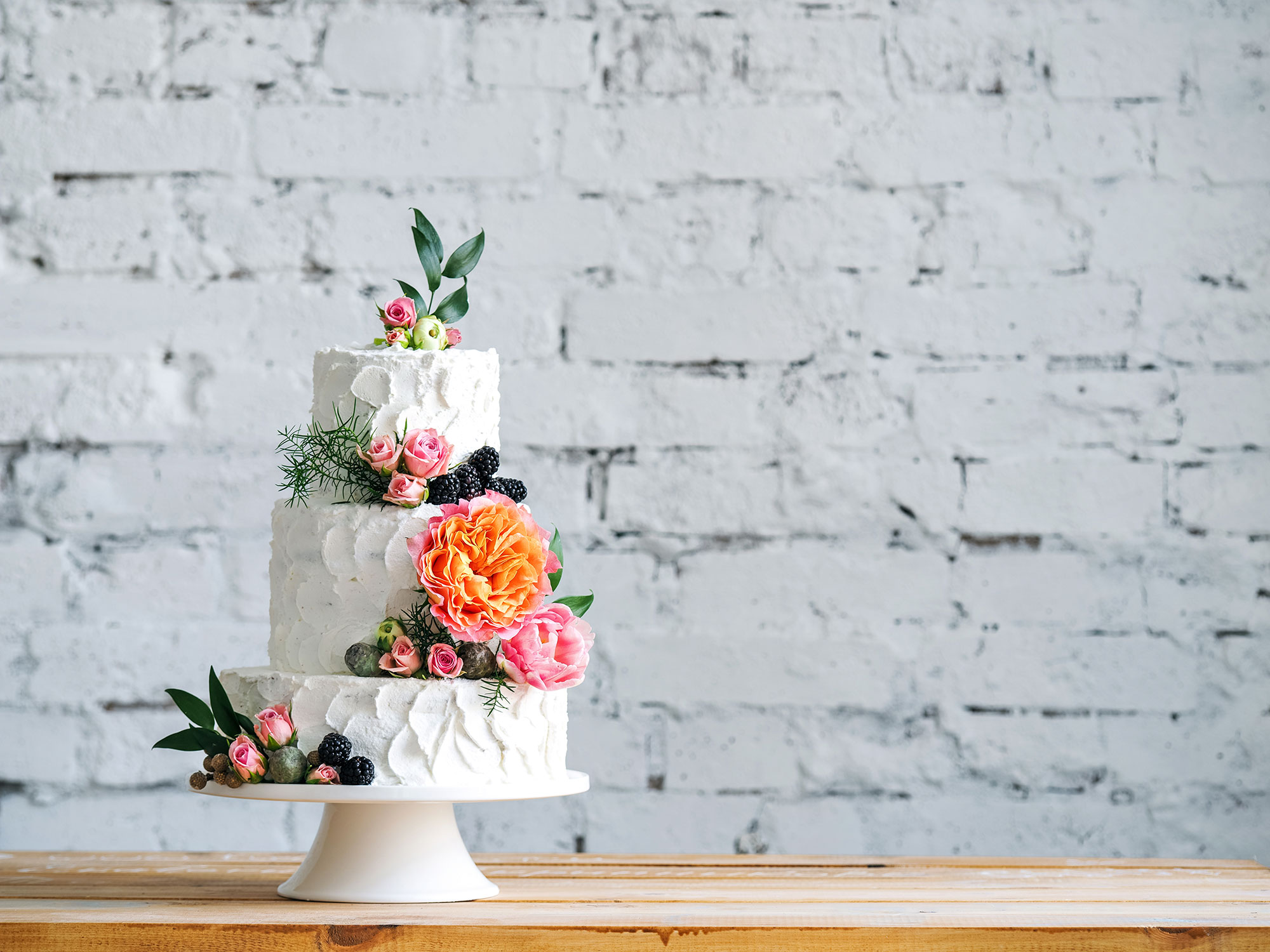 wedding cake covered in flowers against a white brick wall